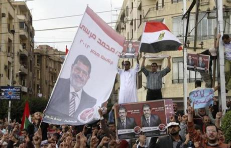 Supporters of president Mohammad Morsi chant and wave his campaign posters and a national flag.